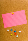 Notecard on corkboard. Bright, blank neon colored notecards on brown corkboard or bulletin board with plastic pushpins, space for copy Stock Photo