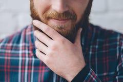 Noten des jungen Mannes mit der Hand sein Bart Lizenzfreie Stockfotografie