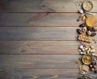 Noten, droge vruchten, honing en oude lepels en vorken op een houten lijstachtergrond stock fotografie