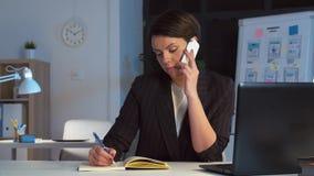 Коммерсантка вызывая на смартфоне на темном офисе акции видеоматериалы