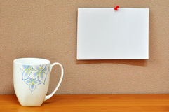 Notepad. A cup of coffee put on the table with a note pad pinned on the board Royalty Free Stock Photo