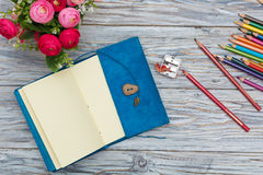 Notepad on aged wood and colored pencils Royalty Free Stock Image