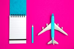 Notepad and airplane on pink background stock image