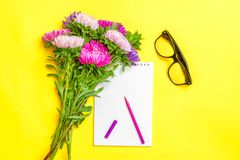 Notepad , aster flowers, colored felt-tip pens, cup with coffee on yellow background. Concept autumn, summer, spring. Place for text.Flat lay.Top view.Copy stock image