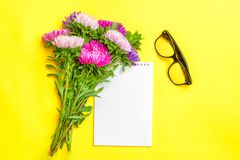 Notepad , aster flowers, colored felt-tip pens, cup with coffee on yellow background. Concept autumn, summer, spring. Place for text.Flat lay.Top view.Copy stock photography