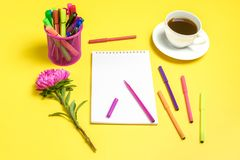 Notepad , aster flowers, colored felt-tip pens, cup with coffee on yellow background. Concept autumn, summer, spring. Place for text.Flat lay.Top view.Copy royalty free stock image