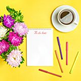 Notepad , aster flowers, colored felt-tip pens, cup with coffee on yellow background. Concept autumn, summer, spring. Place for text.Flat lay.Top view.Copy stock images