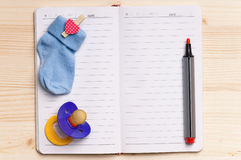 Notepad and baby shoes - top view Royalty Free Stock Image