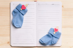 Notepad and baby shoes - top view Stock Photos