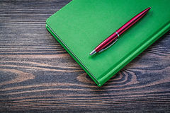 Notepad ball-point pen on wooden board education concept Stock Image
