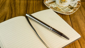 Notepad with ballpoint pen. Coffee cup and flowers stock images