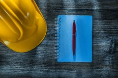 Notepad ballpoint pen hard hat on wooden board.  royalty free stock image