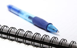 Notepad with a ballpoint pen on top. Closeup Stock Photography