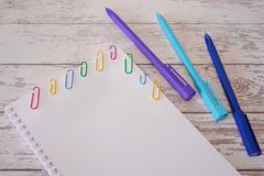 Notepad with blank page and colorful staples and blue pens on a wooden table. Mock up royalty free stock image