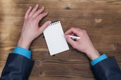 Notepad with blank screen in businessman hands. Business ideas concept. Notepad with copy space and businessman male hands on wooden desk table surface top view Stock Photos