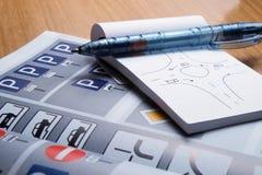 Notepad, bok av trafikregler och penna på en skrivbordtabell royaltyfri bild