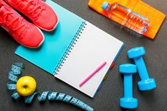 Notepad, a bottle of water, an apple, a skipping rope, dumbbells. Healthy diet, lifestyle, concept of dumbbells. Notepad, a bottle of water, an apple, a skipping Royalty Free Stock Photo