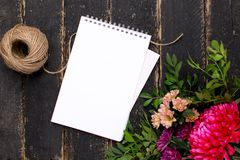 Notepad with a bouquet of flowers on a dark vintage wooden background royalty free stock image