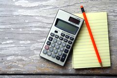 Notepad, calculator and a colorful pencil Stock Photos