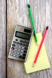 Notepad, calculator and colorful pencils Stock Photos