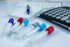 Notepad and calculator next to bottles for samples used in hospitals or medicine for blood samples in a laboratory royalty free stock photography