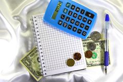 Notepad, calculator, pen and money. Stock Image
