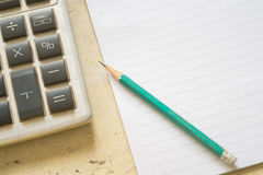 Notepad, the calculator and pencils on a wooden background. Stock Photo