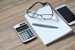 Notepad, calculator, smartphone, glasses and sliver ballpen. On wooden office desk. Selective focus stock image