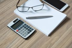 Notepad, calculator, smartphone, glasses and sliver ballpen. On wooden office desk. Selective focus royalty free stock images