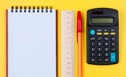 Notepad, calculator and wooden ruler with pen. Royalty Free Stock Image