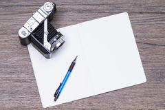 Notepad and camera Royalty Free Stock Image