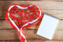 Notepad and candy in the shape of heart Royalty Free Stock Image