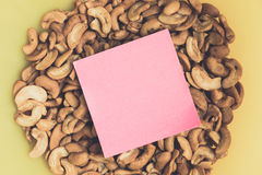 Notepad on Cashew nuts in yellow bowl closeup Stock Image