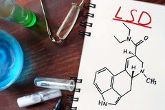 Notepad with chemical formula of LSD. On the wooden table. Drugs concept Stock Photo