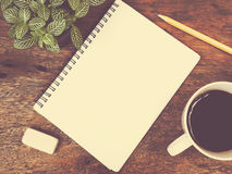 Notepad, coffee and green plant Royalty Free Stock Photo