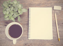 Notepad, coffee and green plant Stock Images