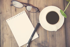 Notepad,coffee,pen and glasses. Working table with notepad, coffee cup , pen , smartphone , glasses and plant Stock Images