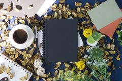 Notepad and coffee on rustic background. Notepad and coffee on rustic blue background with dry flower petals Royalty Free Stock Photo