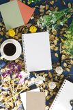 Notepad and coffee on rustic background. Notepad and coffee on rustic blue background with dry flower petals Stock Image