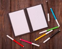 Notepad and colored felt-tip pens on a wooden background. Open notebook and colored felt-tip pens on a wooden background stock images