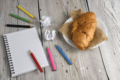Notepad with colored pencils and croissant Royalty Free Stock Image