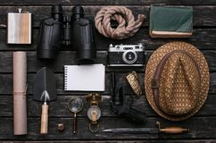 Adventurer accessories. Traveler equipment. Explorer table. Notepad, compass, binoculars, film photo camera, loupe, dagger, handgun, diary book, shovel, rope stock photos
