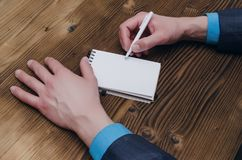 Notepad with blank screen in businessman hands. Business ideas concept. Notepad with copy space and businessman male hands on wooden desk table surface top view Royalty Free Stock Images