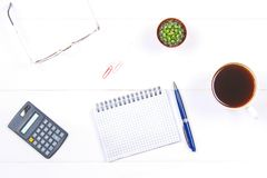 Notepad with copy space. White table with calculator, cactus, note paper, coffee mug, pen, glasses. Royalty Free Stock Photo