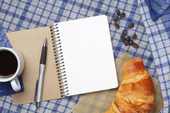 Notepad, croissant and coffee Stock Images