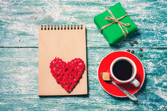 Notepad, cup of coffee, box with gift on a blue wooden table. Space for text Royalty Free Stock Photography