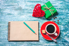 Notepad, cup of coffee, box with gift on a blue wooden table. Space for text Royalty Free Stock Images