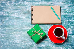 Notepad, cup of coffee, box with gift on a blue wooden table. Space for text Royalty Free Stock Image
