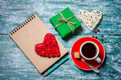 Notepad, cup of coffee, box with gift on a blue wooden table. Space for text Stock Images