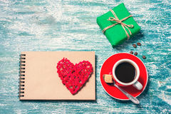 Notepad, cup of coffee, box with gift on a blue wooden table. Space for text Stock Image